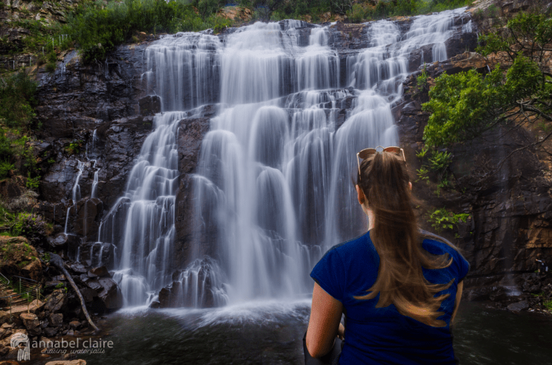Girl sits with MacKenzie Falls in the Grampians National Park in background