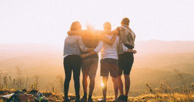 Cuatro personas abrazadas contemplando una puesta de sol