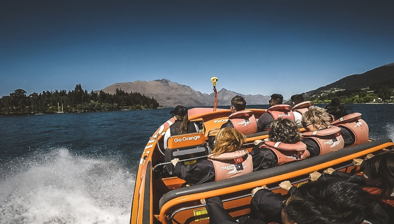 A back view of a group of tourists sitting in a jetboat wearing safety jackets