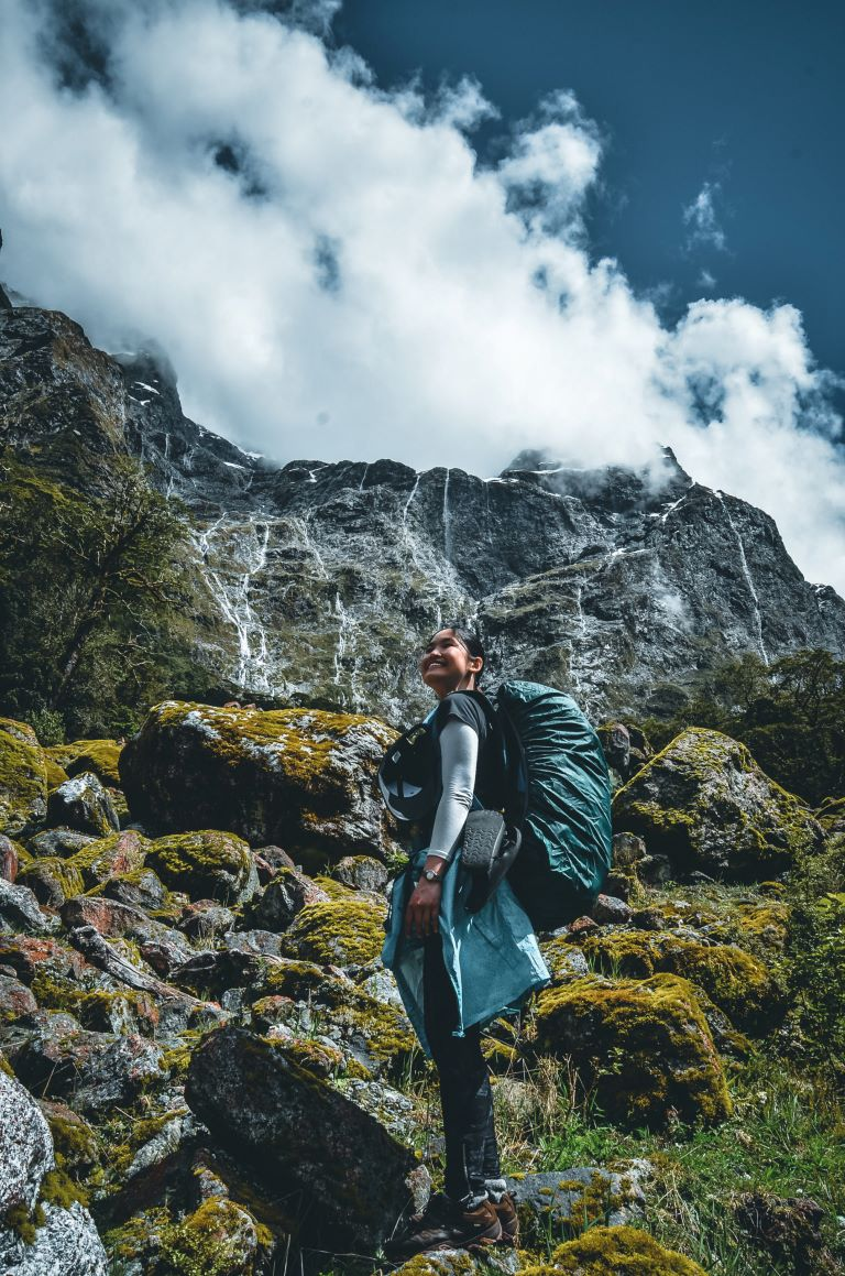 A lady with a blue backpack staring up with waterfall behind her