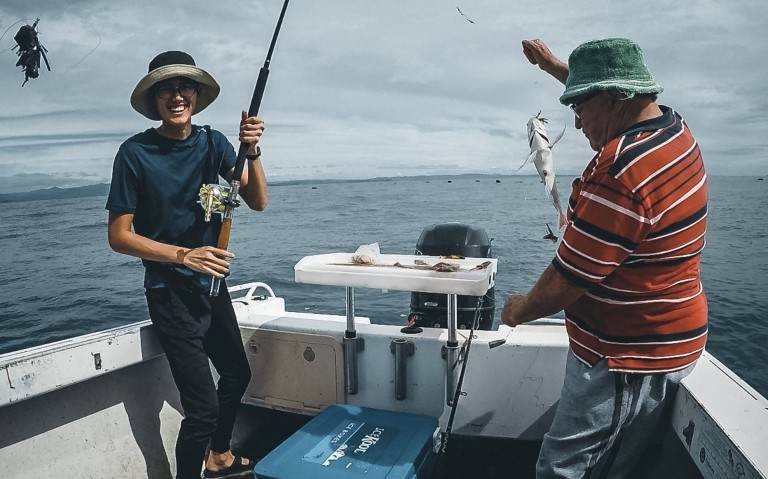 A man smiling into the camera holding his fishing rod while a red shirt man tries to unhook it