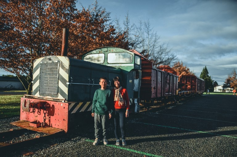 A middle-age couple posing beside an antique train