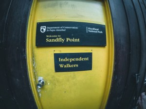 A yellow door with a sign that says Sandfly Point