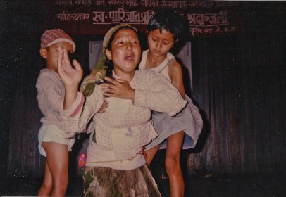 "Chunu Gurung in opera ""Aamako Mutu"" (A Mother's Heart), Kathmandu or Chitwan?, 1993. Banner: All Nepal People's Cultural Organization...Condolences for the death of Writer Parijat."