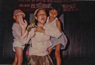 "Chunu Gurung in opera ""Aamako Mutu"" (A Mother's Heart), Kathmandu or Chitwan?, 1993. Banner: All Nepal People's Cultural Organization...Condolences for the death of Writer Parijat."