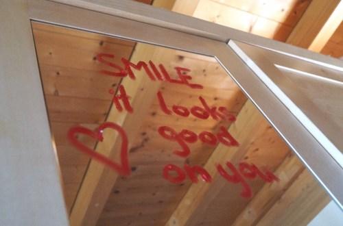 Spiegel, auf dem mit rotem Lippenstift steht: Smile, it looks good on you