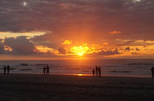 Mehrere Paare stehen am Strand bei Sonnenuntergang