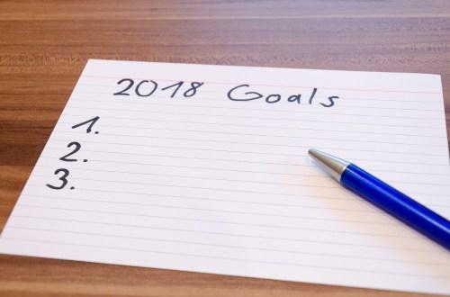 Notizzettel mit aufgeschriebenen Zielen und Stift auf einer Holzplatte