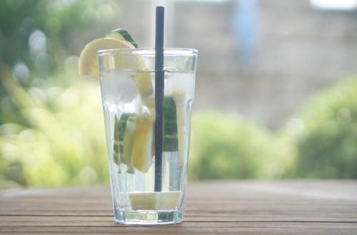Glas mit Zitronen-Gurken-Ingwer-Wasser auf einem Tisch im Garten