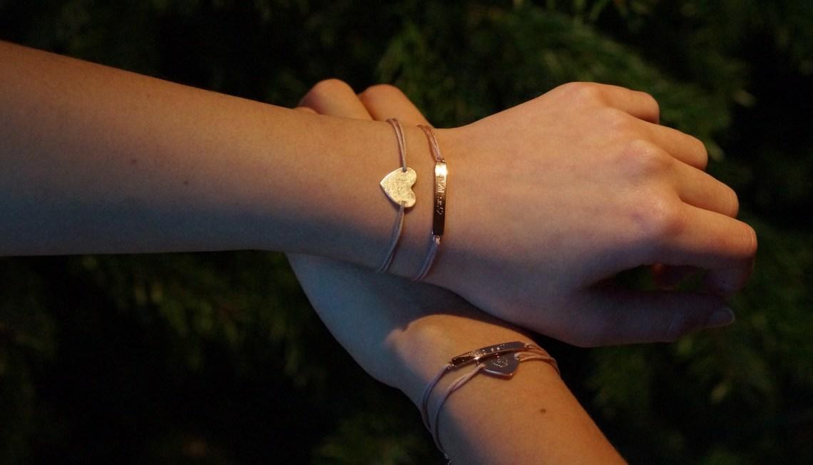 """Zwei Hände mit Armbändern vor einem Weihnachtsbaum, auf der Armbändern ist """"Big sis"""" und """"Lil sis"""" eingraviert"""