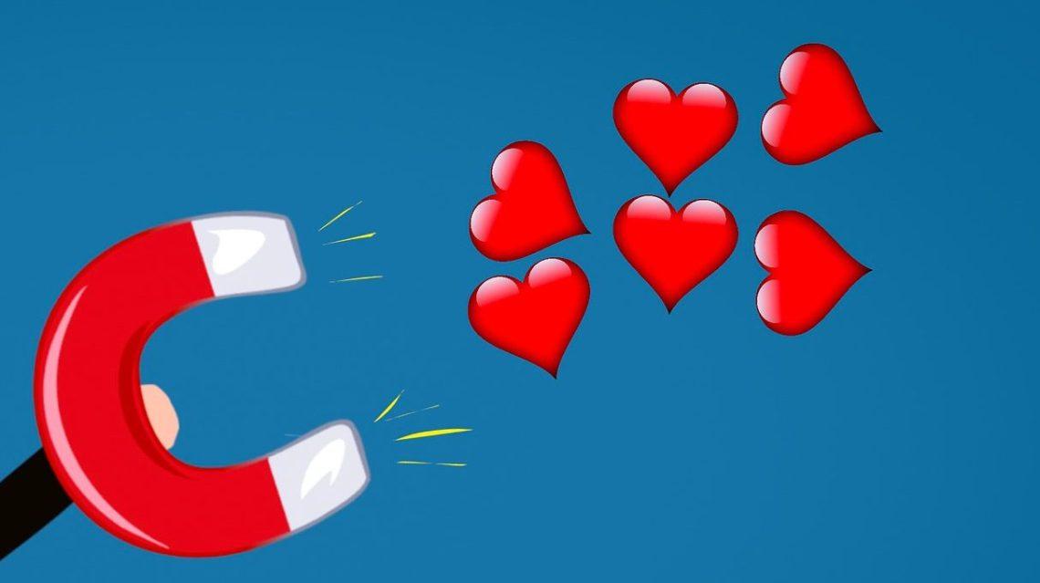 Ein Mann zieht mit einem Magnet Herzen an