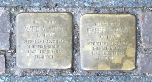 Bronze cobblestone markers of household members deported and killed, in the case of the Heinz sisters at Treblinka.