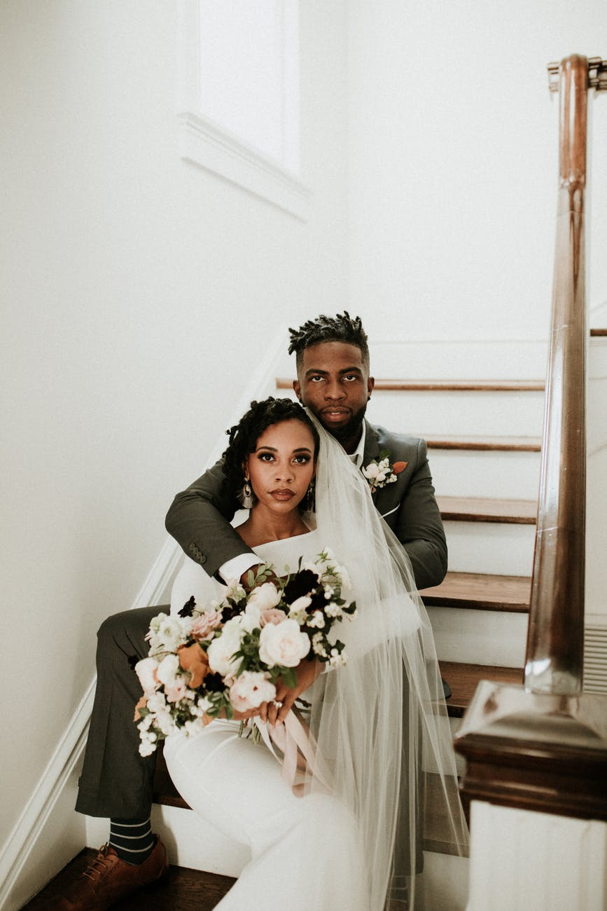 photo of woman wearing bridal gown and husband in suit