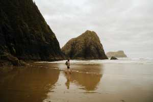 A girl is walking on the san at Crescent Beach in Ecola State Park, Oregon.