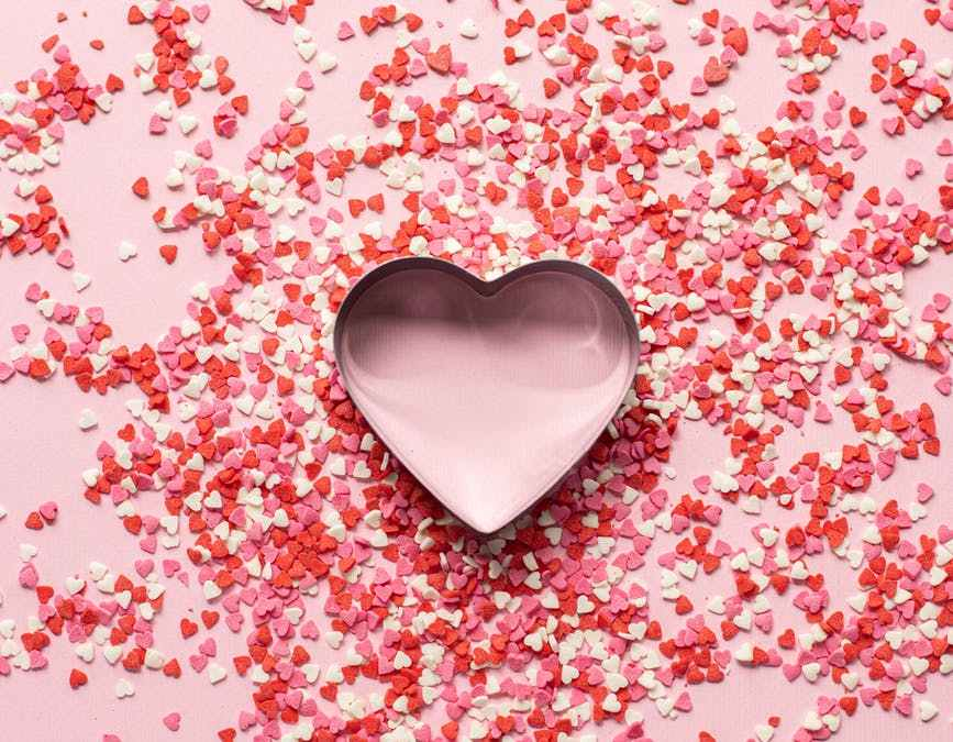 paper confetti in heart shape on pink table