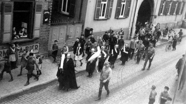 Durante horas seis judíos deben recorrer las calles en ropa de oración y con rollos de Torá de la sinagoga. Son insultados, escupidos y golpeados. La sinagoga es saqueada. Al finalizar todas sus pertenencias son incineradas en la plaza frente al ayuntamiento. Guntersblum, Alemania, 10 nov. 1938.