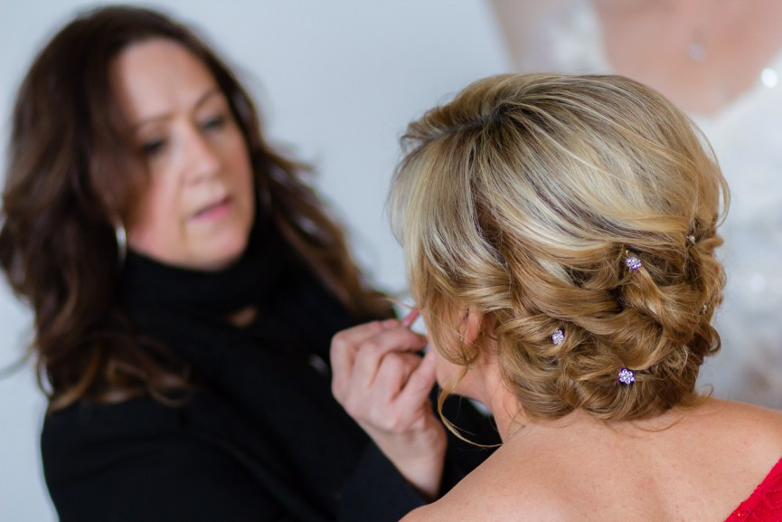 Susan Cormack applying makeup to bridesmaid