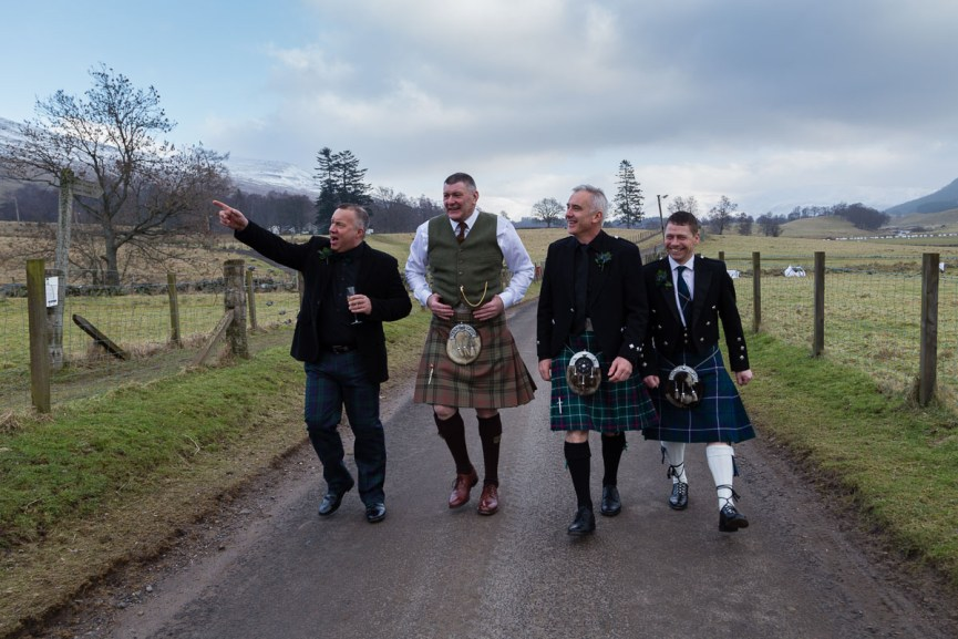 Groom and friends walking near the Glen Clova Hotel