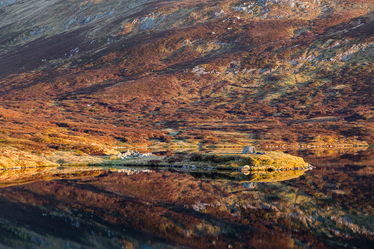 A tent reflects on Loch nan Eun at sunrise
