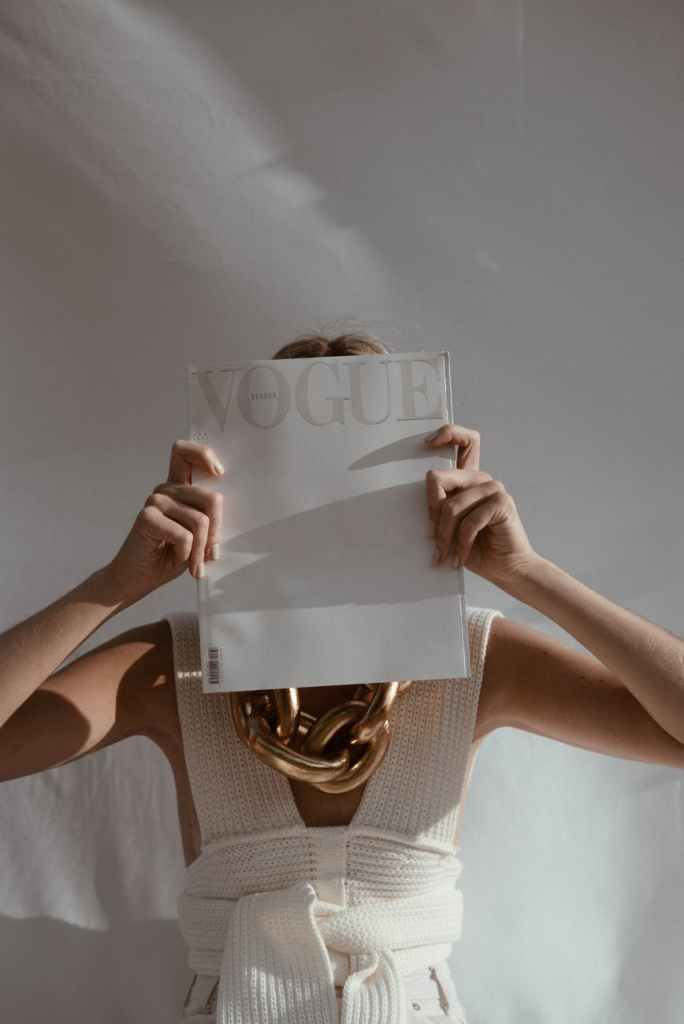 anonymous woman covering face with magazine