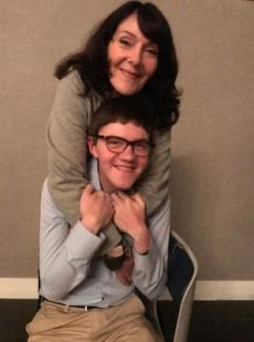Journalism student Hawken Miller is with his mother who his standing over him with her arms around his shoulders.