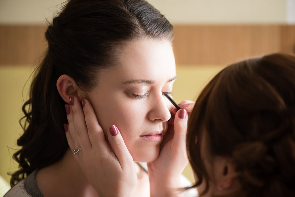 A bride receives help from the artistry of her friend in applying her makeup.