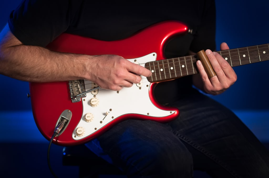 A man plays the blues on a red and white electric guitar.