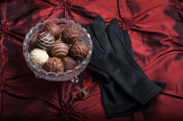 Black gloves are draped next to a glass bowl filled with dark, milk and white chocolate truffles placed on a red, tufted taffeta backdrop.