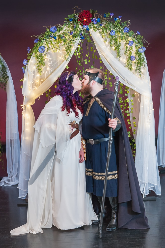 An offbeat bride and groom kiss underneath a canopy.
