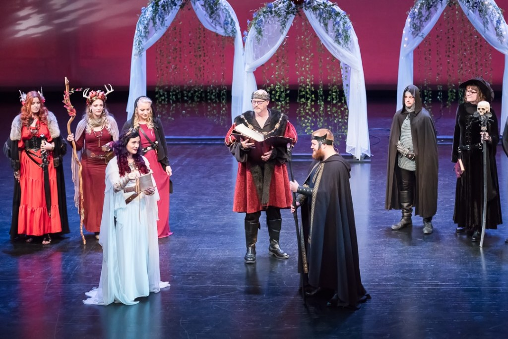 A bride and groom in high-fantasy style, exchange vows on a local theater in the presence of their Dungeon Master and attendants.