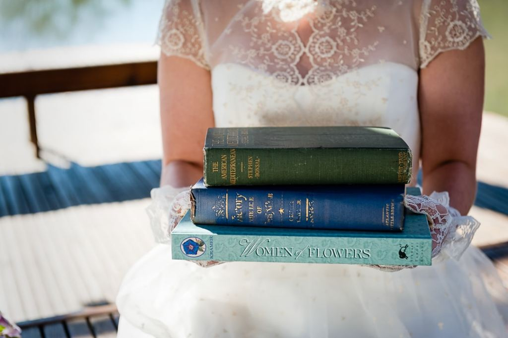 A bride holds a stack of books which will be used as her wedding centerpieces.