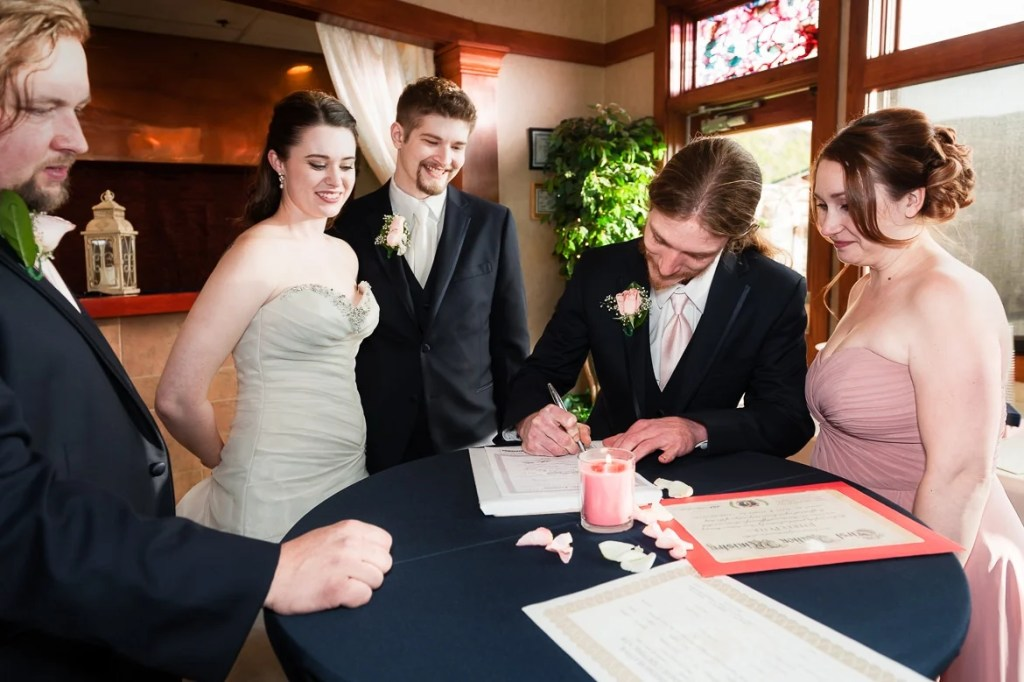A wedding couple, their officiant and members of the bridal party sign the marriage license.