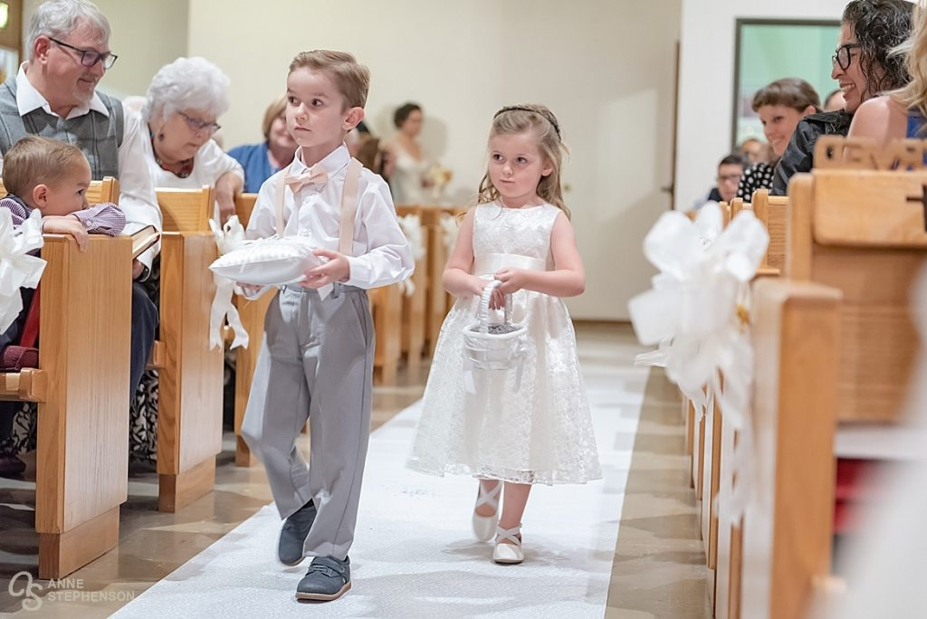 The ring bearer and flower girl proceed down the aisle, marking the arrival of the bride.