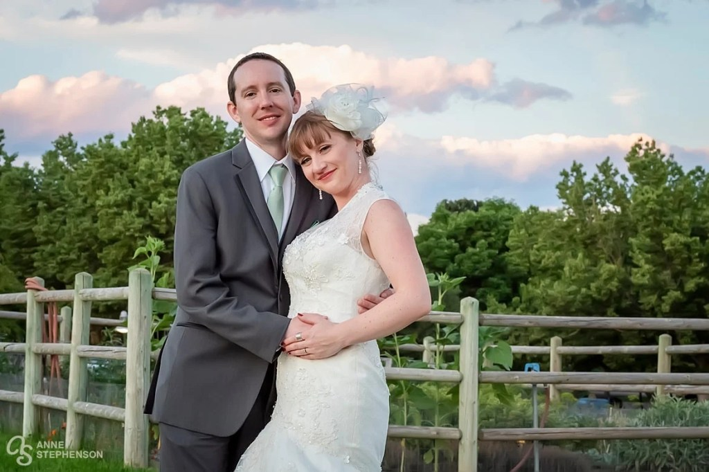 The wedding couple in front of a garden with beautiful clouds in the background at the Lakewood Heritage Center.