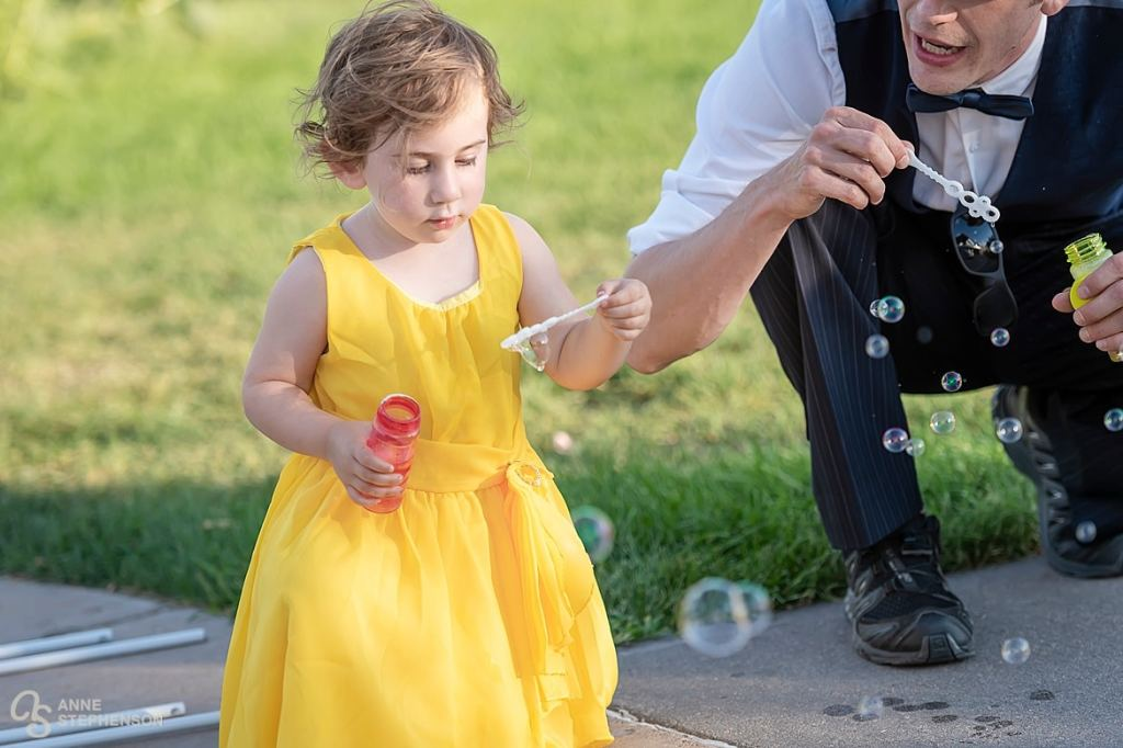 The flower girl takes a break to blow bubbles with one of the groomsmen.