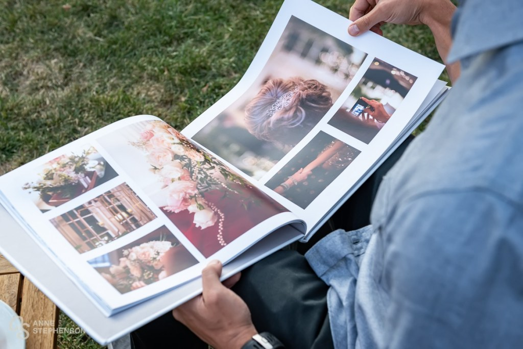 A guest pages through the bride and grooms wedding photo album.
