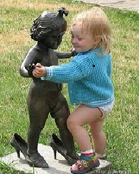 Child dancing with a sculpture