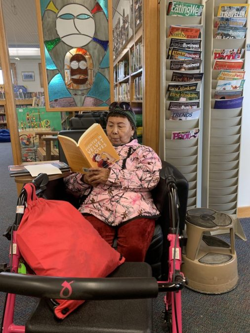 Alaskan Native elder reading Fighter in Velvet Gloves
