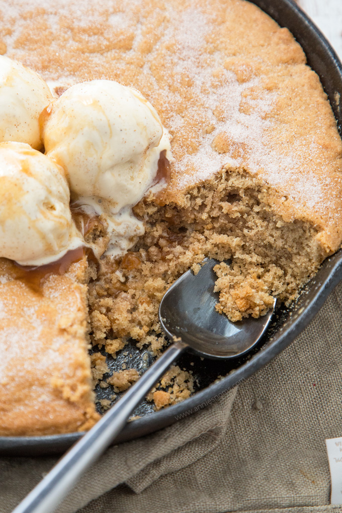 A thick and chewy snickerdoodle cake baked in a cast iron skillet and topped with ice cream and caramel sauce.
