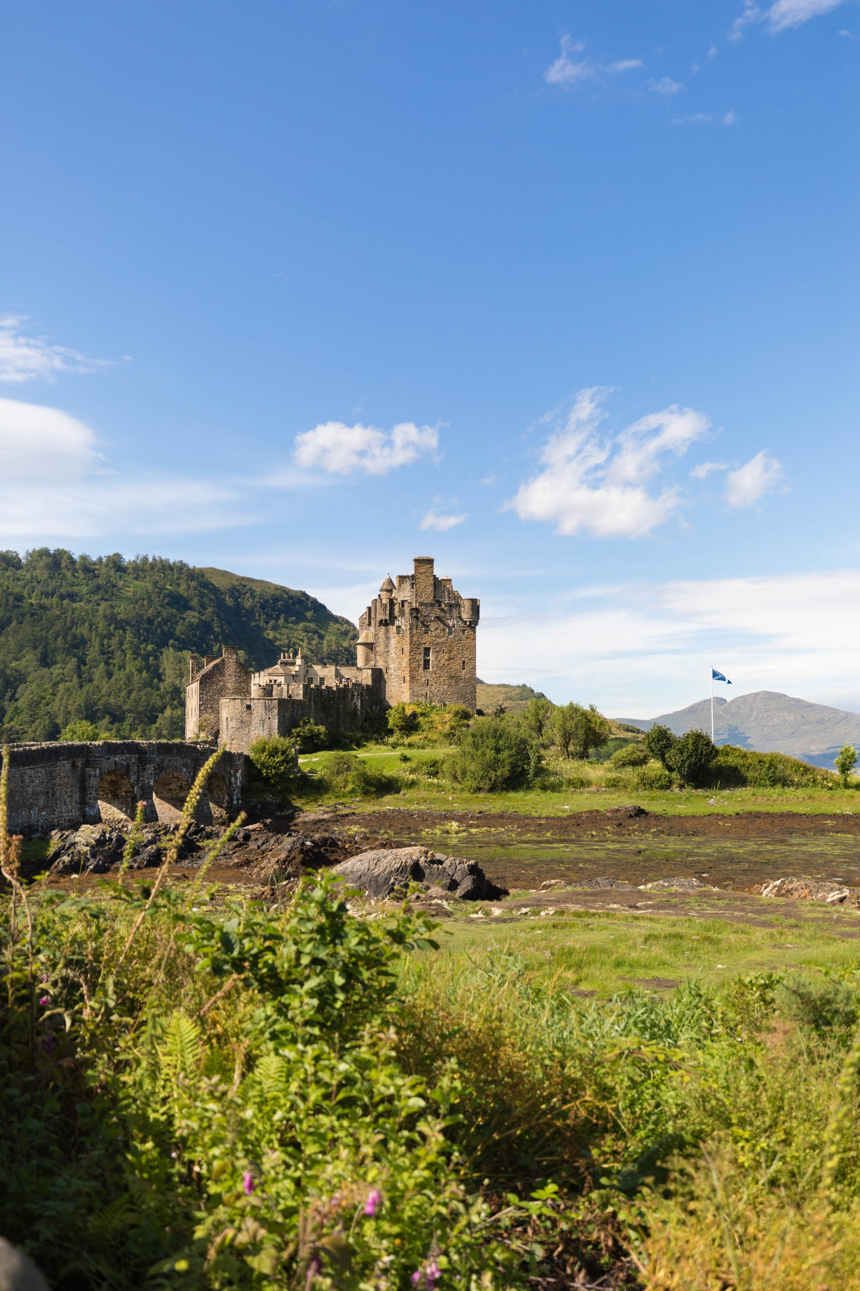Eilean Donan Castle Bridge and Scottish Flag in Isle of Skye Scotland by Annie Fairfax