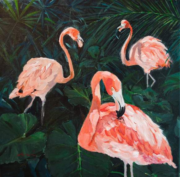 three flamingos in tropical garden