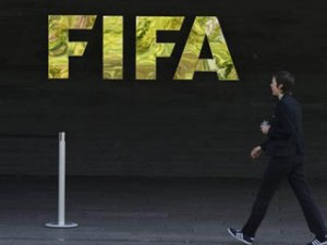 A woman walks by a logo of international soccer's top body FIFA, on May 27, 2015 at the organization's headquarters in Zurich. Swiss policeraided a Zurich hotel to detain six top football officials as part of a US investigation into tens of millions of dollars of bribes paid to sport leaders, Swiss authorities and media reports said.  AFP PHOTO / FABRICE COFFRINI        (Photo credit should read FABRICE COFFRINI/AFP/Getty Images)