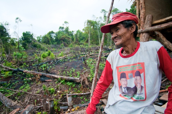 A villager standing with cleared landed in the background. East Kalimantan, Indonesia. Photo by Moses Ceaser for Center for International Forestry Research (CIFOR).