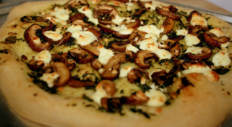 Pesto pizza with cremini mushrooms and goat cheese.