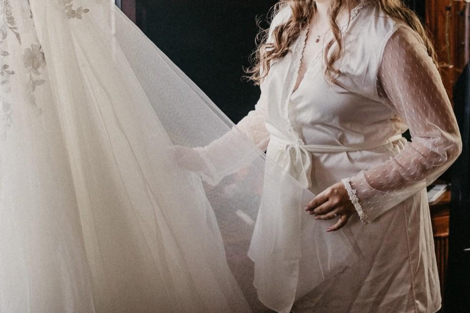 Bride admiring her wedding dress before her Asheville elopement.