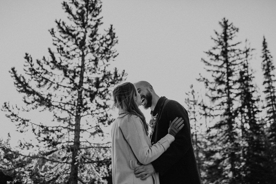 Man smiling at his fiancée during their Rocky Mountain National Park engagement photos.