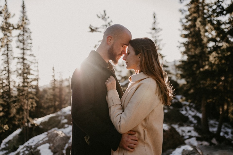 Couple pressing foreheads together during their Rocky Mountain National Park engagement photos.