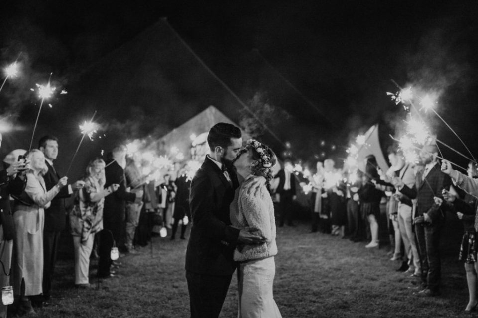 Couple kissing during their sparkler exit.