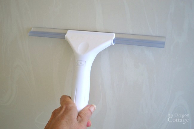 A squeegee works to clean smooth shower walls