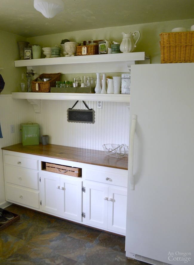 Cottage Farmhouse Laundry-Mudroom Makeover after-mudroom area with room for gardening supplies and freezer.